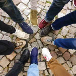 Image of legs of people standing in a circle and pointing their toes to each other.