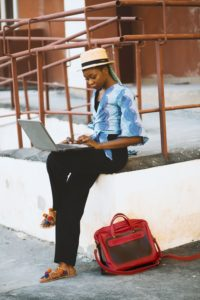 Woman sitting on edge of white concrete stairs and looking at her laptop.