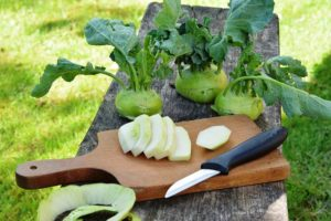 sliced and whole Kohlrabi sitting on a cutting board. There is a knife placed beside them.