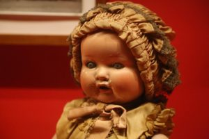 Antique doll wearing a bonnet and dress.