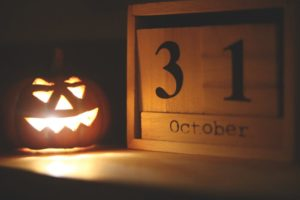 Jack-o-lantern with a light burning inside of it is sitting next to a wooden calendar that says October 31
