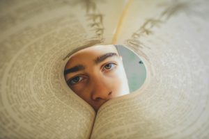 The pages of a book have been bent into a circle. A person's face is staring at you from the other end of that circle.