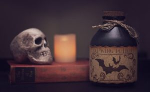 Potion in the foreground. Skull and lit candle sitting on a book in the background.