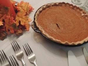 Pumpkin pie, forks, and a decorative gourd sitting on a Thanksgiving supper table