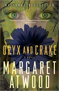 Oryx and Crake by Margaret Atwood book cover. Image is of a woman's face and a flower.