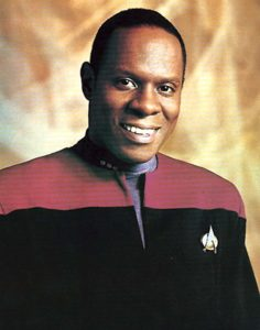 Avery Brooks as Captain Benjamin Sisko in Star Trek: Deep Space Nine. Photo is of Avery smiling while wearing Star Trek uniform.