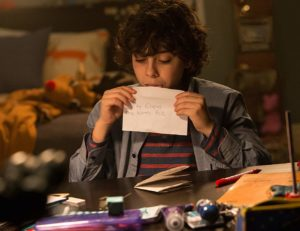 Emjay Anthony as Max Engel. He is licking an envelope in this scene.
