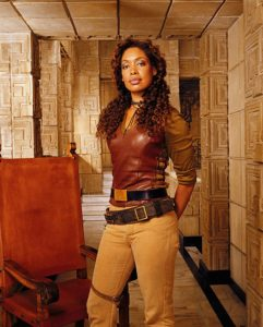 Gina Torres as Zoe Washburne from Firefly. She's standing by a chair in this photo.