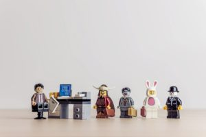 Lego people standing in a tidy queue while waiting to talk to someone who is sitting behind a desk.