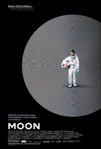 Moon film poster. Image on it is of an astronaut wearing a spacesuit and holding his helmet.