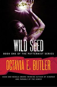 Wild Seed by Octavia E. Butler book cover. Image on cover is of woman holding a glowing root.