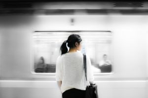 Woman standing and waiting for a subway car to stop