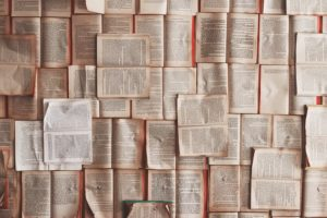 Opened books lying down on a flat surface. Every inch of the surface is covered in books.