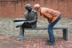 man peering at statue of other man who is reading a newspaper.