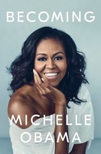 Becoming by Michelle Obama book cover. Image on the front of it is of Mrs. Obama smiling and looking straight ahead at the viewer.