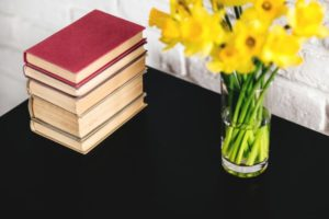Stack of books sitting next to a vase of yellow flowers