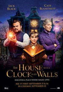 Poster for the film The House with a Clock in Its Walls. The three main characters from that film are smiling and looking straight ahead in it. One is holding a book and the other holds a light.