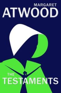 The Testaments by Margaret Atwood book cover. Image on cover is of a handmaid wearing a green shawl and white cap. You can't see her face.