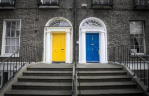 two front doors in a duplex. One door is blue and the other one is yellow