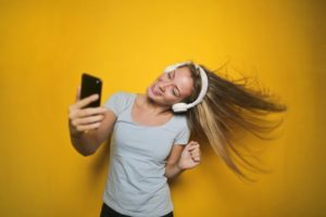 Woman dancing while using headphones and iPhone