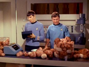 Leonard Nimoy as Mr. Spock and and Deforest Spark as Dr. McCoy. They are looking over a table filled with tribbles.