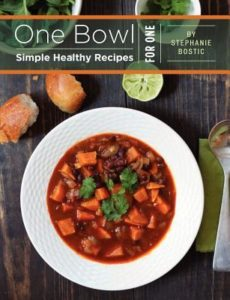 One Bowl: Simple Healthy Recipes for One by Stephanie Bostic. Book cover is of a bowl of hearty vegetable soup. There are two bread rolls, a lime, and a spoon sitting next to it.