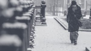 Woman walking down a city street during a blizzard