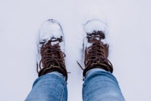 Person wearing brown boots and blue denim. The're standing on snow and their boots are caked in snow.