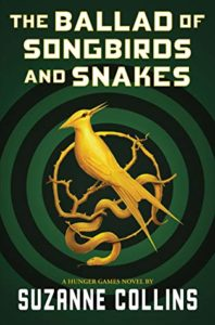 The Ballad of Songbirds and Snakes by Suzanne Collins book cover. Image on cover is of a gold mocking jay sitting on a branch. There is a target sign behind it.