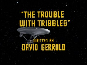 Text says The Trouble with Tribbles written by David Gerrold. Image in the background is of the Enterprise from Star Trek: The Original Series.