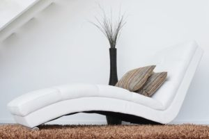 A white chaise lounge. It has two pillows on it and is sitting next to a vase filled with dead branches.