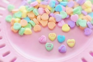 "A pink plate covered in candy conversation hearts. The six hearts we can read say ""soul mate,"" love bug,"" ""sweet talk,"" ""say yes,"" ""love,"" and ""xoxo."""