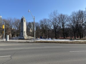 Landscape photo of a park. Image on left is of a World War I statue. There are numerous trees in the background and a road in the foreground.
