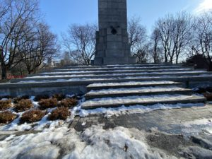 Close-up photo of snow sitting on the steps of a World War I monument.