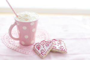 a hot chocolate topped with whipped cream sitting in a pink, polka dotted mug. There are two heart-shaped cookies sitting on a doily next to the mug.