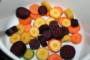 A bowl full of orange, yellow, green, and purple carrots sliced into round pieces.