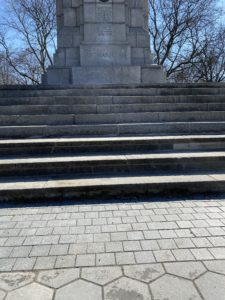 Photo of a World War I monument at a Toronto park. There are bare tree branches in the background and dry steps leading up to the monument in the foreground.