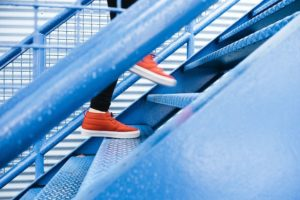 Photo of person's legs and orange shoes as they climb a flight of blue stairs.