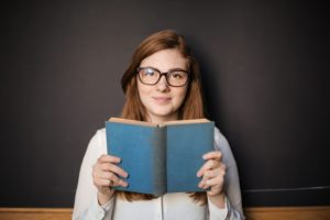 Woman holding a book and smiling