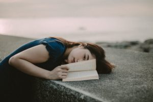 photo of woman lying down on a stone wall while holding the pages of a book open.