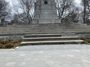 A photo of a statue in a park. There are steps leading up to the statue and the bushes around it are still dormant from the winter.