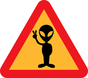 A caution sign with the outline of an alien giving a peace sign on it.