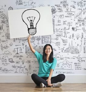 Asian woman holding up a drawing of a lightbulb while sitting next to a white wall filled with sketches of various ideas.