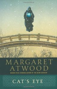 Cat's Eye  by Margaret Atwood book cover. Image on cover is of a hooded figure holding a glowing blue orb levitating above a bridge while snow falls on bare tree branches.