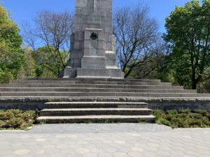 Close-up shot of a moment. There are green trees in the background and green bushes in the foreground next to the steps on the monument.