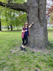 Woman leaning up against a massive elm tree, smiling, and pointing at it.