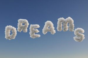Six clouds digitally altered to spell out the word dreams against a blue sky