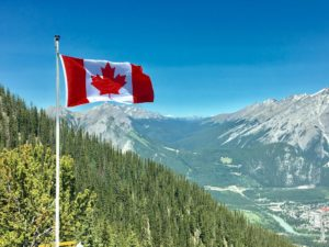 A canadian flag flying with mountains and pine forests in the background.