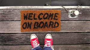 "A snapshot of the legs and feet of someone wearing jeans and red sneakers. They're standing next to a ""welcome on board"" mat on what appears to be a wooden pier."