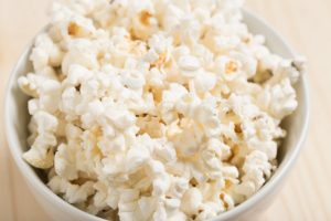 A white bowl filled with popcorn and sitting on a wooden table
